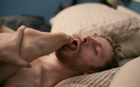 Sebastian licking Eden's foot in Bed Party, a porn movie directed by Shine Louise Houston for Pink And White Productions