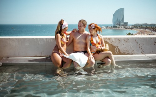 Ryan James and two young women flirting in a pool by the sea in an Erika Lust/XConfessions erotic movie, a pick by Blue Artichoke Films' in