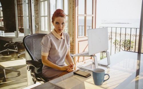 Amarna Miller in vintage workwear sitting at a desk in Erika Lust/XConfessions erotic movie, a pick by Blue Artichoke Films' in