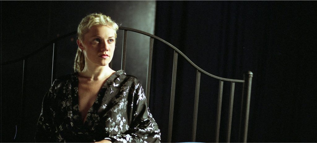 Alicia Whitsover waits onstage on the bed  in her bathrobe in Matinee, an erotic film directed by Jennifer Lyon Bell for Blue Artichoke Films