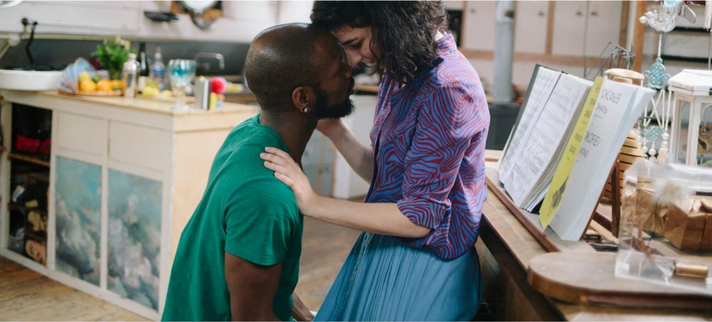 Bishop Black and Anne De Winter kiss on the piano in in Second Date, a VR 360° 3D immersive virtual reality erotic movie directed by Jennifer Lyon Bell for Blue Artichoke Films