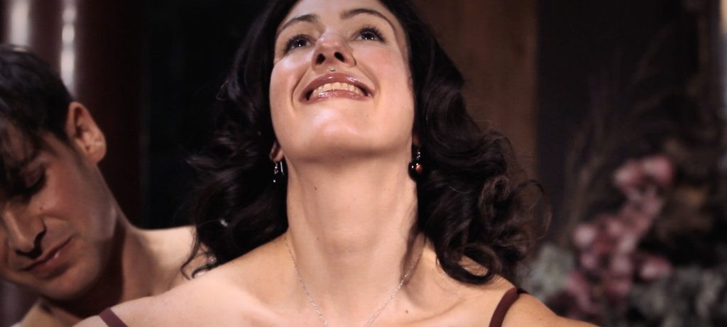 Sadie Lune smiles happily while Parker Marx dresses her in a bra in Adorn, an erotic game film directed by Jennifer Lyon Bell for Blue Artichoke Films